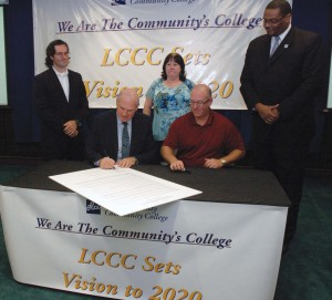 Lorain County Community College President Roy Church (seated left) signs the resolution establishing the new strategic plan - Vision 2020 - for LCCC after LCCC Board of Trustees Vice Chairman Ben Fligner finished signing the document. The Board approved the strategic plan at its Thursday meeting. Watching (standing from left) is Michael Bruckman , director of research for NanoBio Systems, a Boston company that moved its operations to the LCCC Desich SMART Center; Charlene Dellipoala, an LCCC and University Partnership graduate and current master's degree student, and Marty Eggleston, LCCC men's basketball coach and student success coach.
