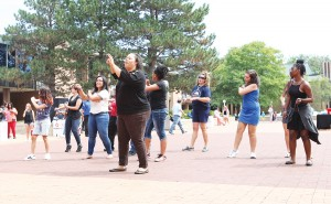 Kionna McIntos-Pharns, staff assistant to the vice president, leads a group of students in a dance during the All-College picnic on Aug. 26.
