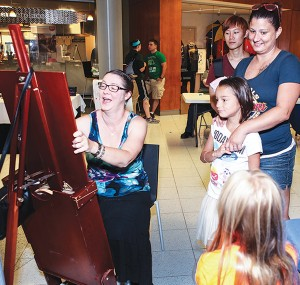 Jessica Justice, wraps her arms around her daughter Atheena as her daughter Paige has her caricature drawn.