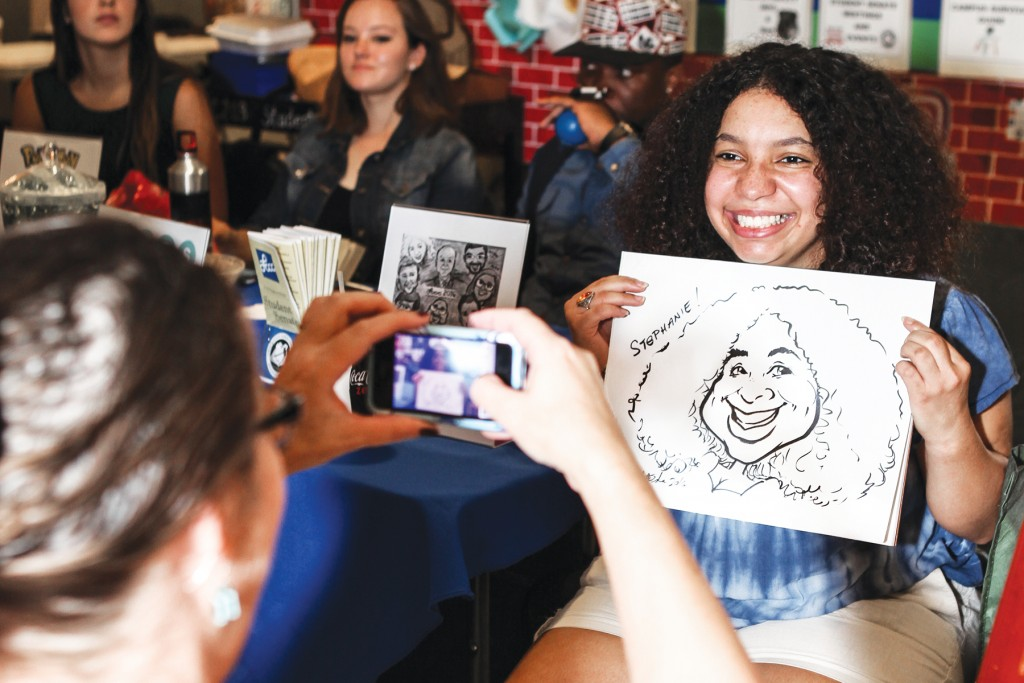 Artist Wendy Fredan photographs sixth-year culinary arts major Stephanie Herndon on Aug. 23 during Welcome Week on the campus of Lorain County Community College. Fedan has been drawing caricatures for over 20 years.