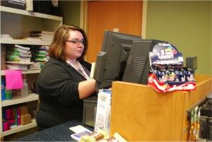 Commodore Bookstore student employee, Mary Plumley, works at one of the registers at the front of the college bookstore.